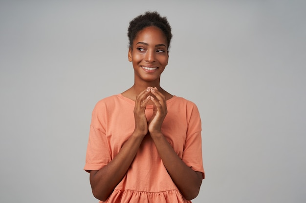 Positieve jonge aantrekkelijke bruinharige krullende vrouw met breed lachend terwijl ze sluw opzij kijkt en gevouwen handen onder haar kin houdt, geïsoleerd over grijze muur