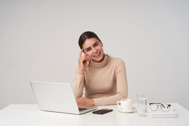 Positieve jonge aantrekkelijke brunette zakenvrouw met paardenstaart kapsel haar gezicht aanraken met opgeheven hand zittend over witte muur en vrolijk glimlachen
