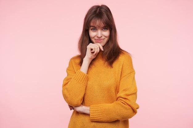 Positieve jonge aantrekkelijke donkerharige vrouw in mosterd gebreide trui die met charmante glimlach kijkt en opgeheven hand op haar kin houdt, geïsoleerd over roze muur