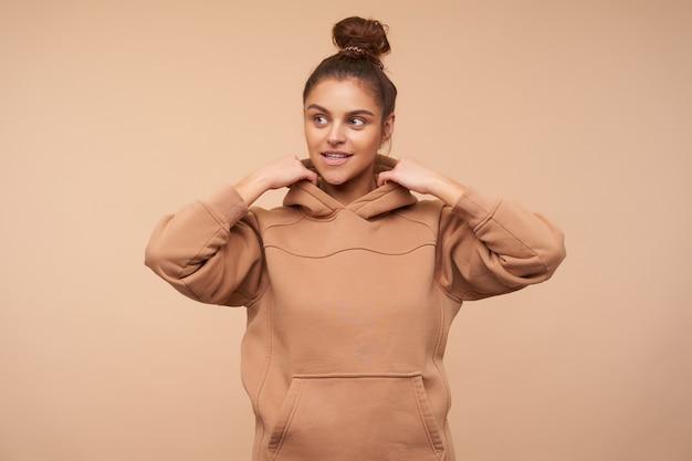 Positieve jonge aantrekkelijke vrouw die haar bruin haar in knoop draagt terwijl ze over beige muur staat, opzij kijkt met een lichte glimlach en haar handen opheft naar haar kap