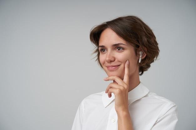 Positieve jonge aantrekkelijke vrouw met kort kapsel die een wit overhemd draagt terwijl ze staat, opzij kijkt met een charmante glimlach en de wijsvinger op haar wang houdt