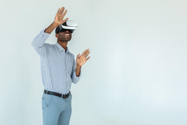 Positieve jonge afro-amerikaanse man met behulp van vr-bril terwijl hij tegen een witte muur staat