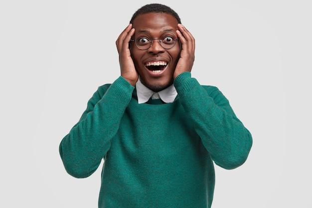 Positieve jonge afro-amerikaanse man voelt zich dolgelukkig als hij een geldbeloning ontvangt voor goed ijverig werk, de handen op het hoofd houdt, glimlacht breed