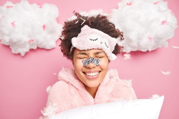 Positieve jonge afro-amerikaanse vrouw glimlacht toothily houdt de ogen gesloten geniet 's ochtends na een goede nachtrust draagt slaappak blinddoek op voorhoofd houdt kussen houdingen tegen vliegende veren