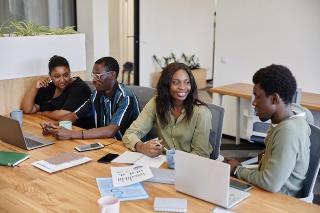 Positieve jonge afro-amerikaanse zakenmensen praten aan grote vergadertafel