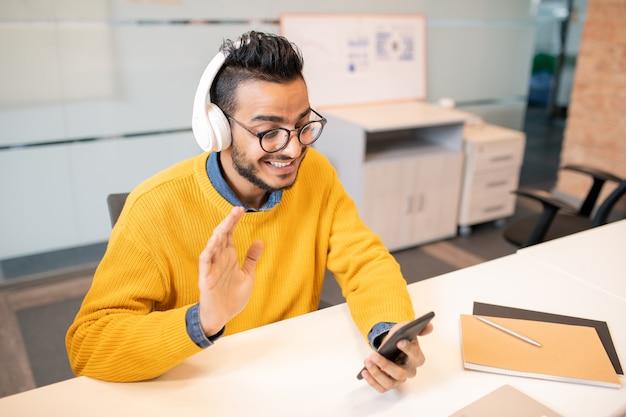 Positieve jonge arabische bedrijfsspecialist in brillen die aan bureau zitten en collega begroeten terwijl ze face-to-face communicatie hebben via mobiele app