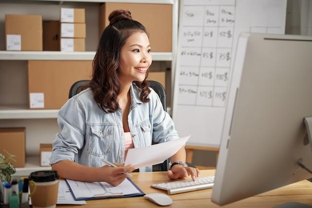Positieve jonge aziatische logistiekspecialist die op kantoor werkt en online bestand bewerkt tijdens het verwerken van de aanvraag