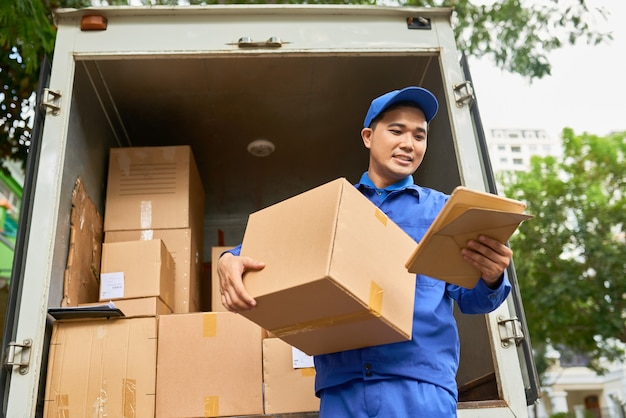 Positieve jonge aziatische man die post levert en adres- en pakketgegevens op tabletcomputer controleert