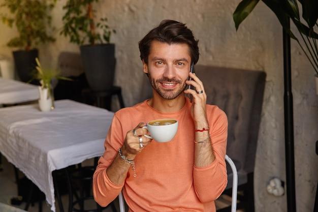 Positieve jonge bebaarde man met donker haar kijkt vrolijk en houdt een kopje koffie, bellen zittend in het stadscafé