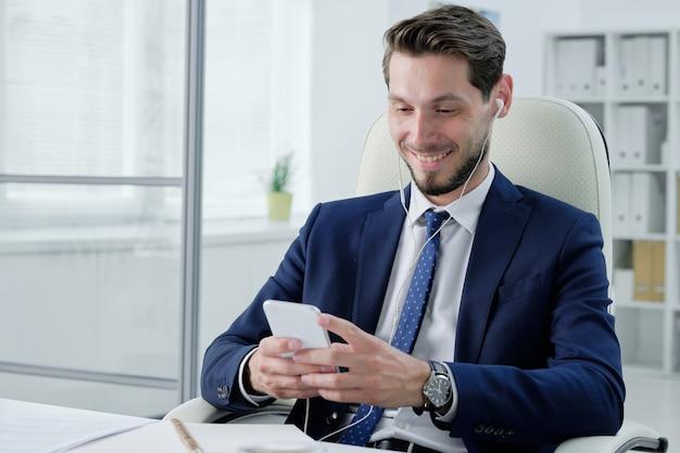 Positieve jonge bebaarde zakenman in oortelefoons zittend op een bureaustoel en telefoon controleren terwijl u naar muziek luistert