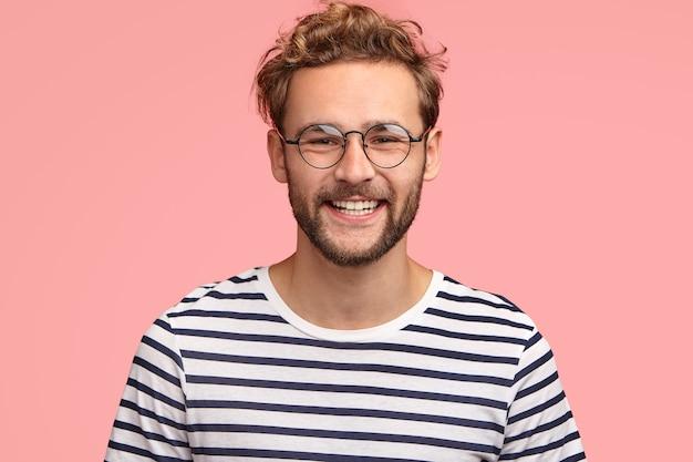 Positieve jonge blanke man met prettige vriendelijke glimlach, toont witte tanden, verheugt zich op een nieuwe levensfase, draagt een casual gestreepte trui en ronde bril, staat alleen tegen een roze muur.