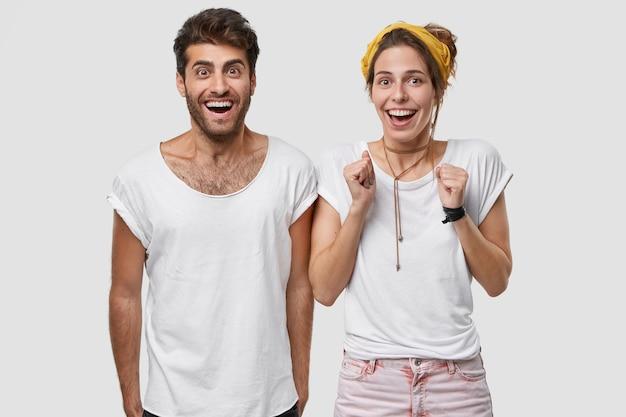 Positieve jonge blanke vrouw balde vuisten, draagt t-shirt, kijkt met ingehouden adem, staat in de buurt van vrolijke man, viert succes en triomf