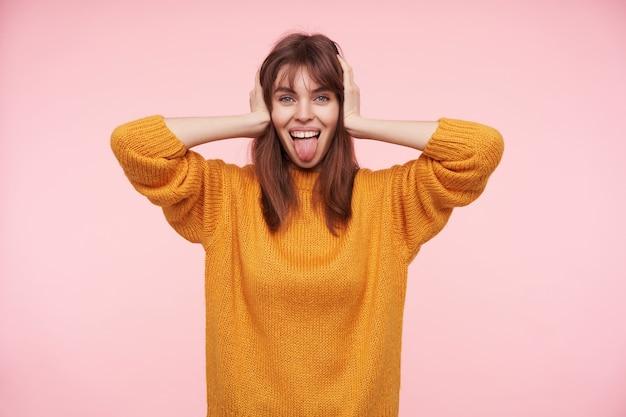 Positieve jonge blauwogige donkerharige dame die haar oren bedekt met opgeheven handpalmen en opgewekt kijkt, haar tong uitsteekt terwijl ze poseert over roze muur