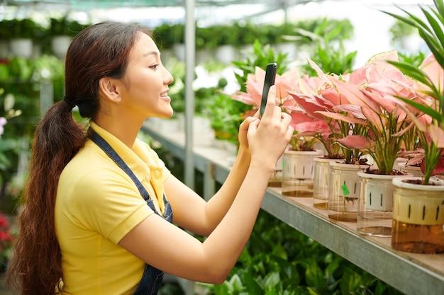 Positieve jonge bloemenkwekerijmanager die foto's van bloemen op smartphone maakt om op sociale media te plaatsen