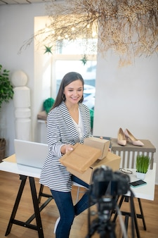 Positieve jonge blogger die lacht terwijl ze cadeautjes vasthoudt voor haar volgers