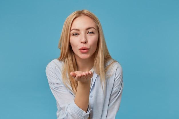 Positieve jonge blonde vrouw met casual kapsel poseren, palm verhogen en blazen lucht kus met samengeknepen lippen, blauw shirt en grijs t-shirt dragen