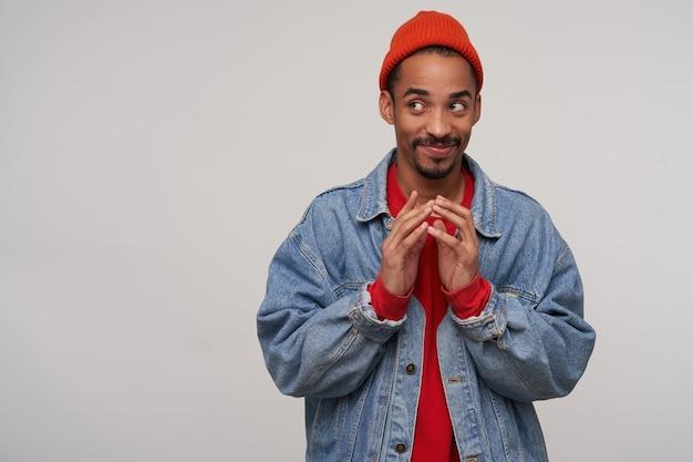 Positieve jonge bruinogige, bebaarde brunette man met donkere huid speels opzij kijkend met een lichte glimlach en vouwende opgeheven handen, staande tegen een witte muur