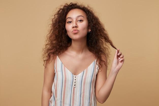Positieve jonge bruinogige brunette dame trekt haar krullend haar met opgeheven hand en vouwen lippen in lucht kus, poseren op beige in riem gestreepte blouse