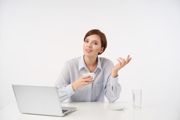 Positieve jonge bruinogige kortharige brunette dame gekleed in formele kleding met keramische beker in opgeheven hand en het verhogen van de palm terwijl poseren op wit