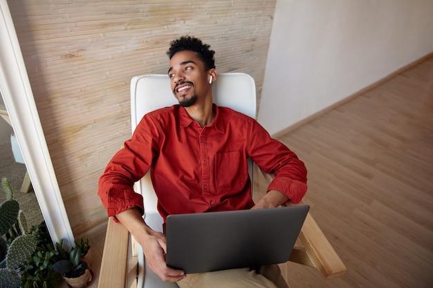 Positieve jonge brunette bebaarde donkere man in rood shirt leunt zijn hoofd achterover zittend in een stoel en kijkt vrolijk uit het raam, geïsoleerd op interieur