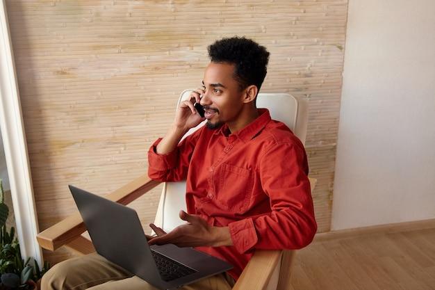Positieve jonge brunette bebaarde donkere man met trendy kort kapsel bellen met zijn smartphone zittend in een stoel op interieur en licht glimlachend