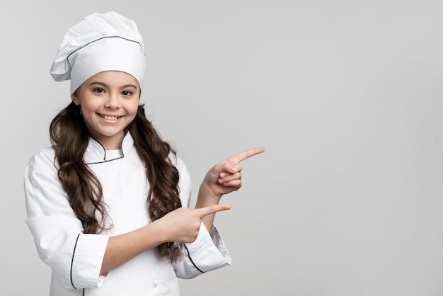 Positieve jonge chef-kok die met exemplaarruimte glimlacht