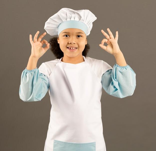 Positieve jonge chef-kok die ok teken toont