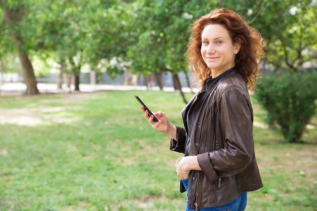 Positieve jonge dame die smartphone in stadspark gebruiken