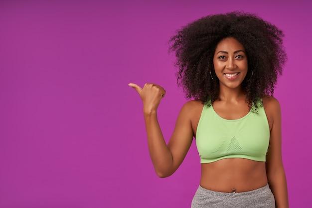 Positieve jonge donkere vrouw met krullend haar sportieve kleding dragen, poseren op paars met opgeheven hand en opzij tonen met duim met blije en brede glimlach