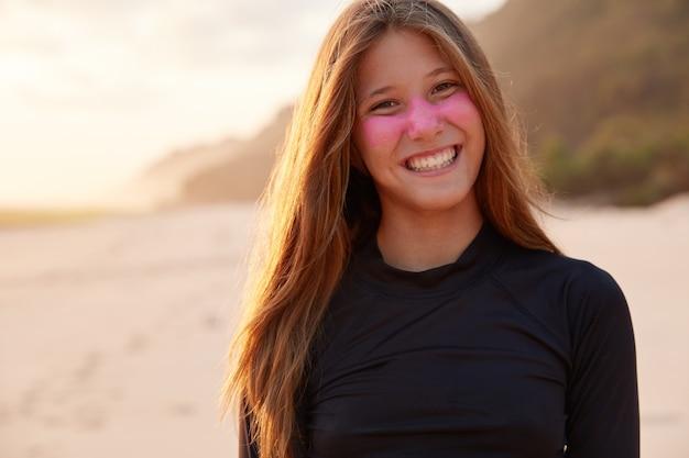 Positieve jonge ervaren surfer glimlacht breed, beschermt gezicht zinkdioxide