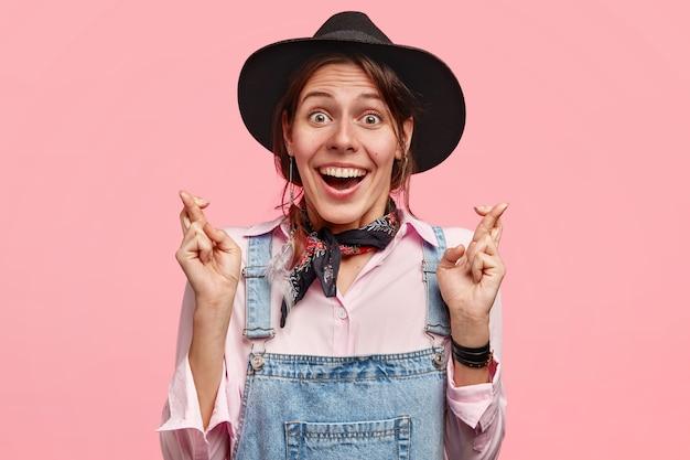Positieve jonge europese landarbeider heeft een brede glimlach, toont witte tanden, kruist vingers van groot verlangen haar dromen komen uit