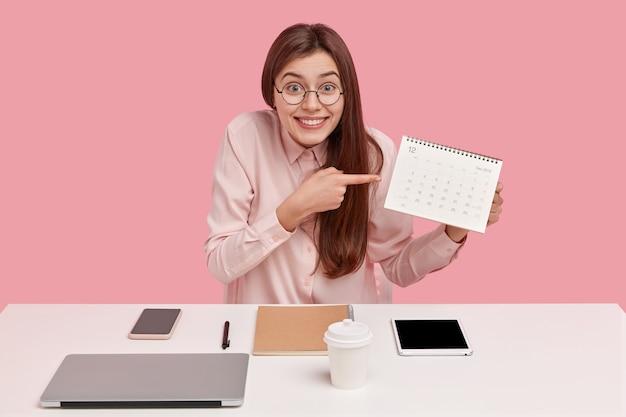 Positieve jonge freelancemedewerker wijst op de kalender, toont de datum van het afronden van projectwerk, gekleed in modieuze kleding, poseert op het bureaublad
