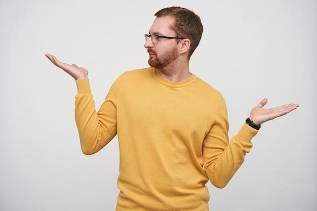 Positieve jonge hansome brunette man met baard en kort kapsel, het dragen van een bril en mosterdpullover terwijl hij met opgeheven handpalmen staat