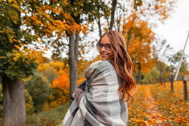 Positieve jonge hipster vrouw in een modieuze geruite gebreide sjaal in een stijlvolle bril met een trendy kapsel wandelingen in het park op een warme herfstdag tussen de bomen in geeloranje gebladerte.