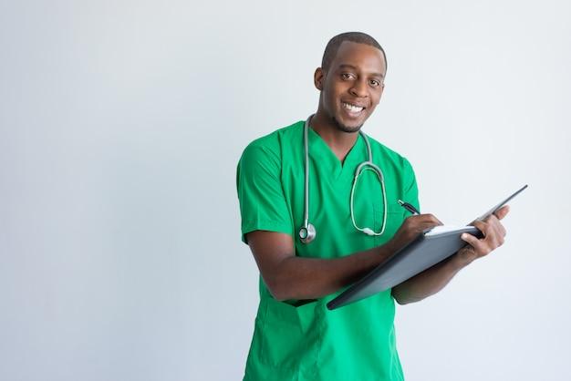 Positieve jonge huisarts die medisch dossier invullen.