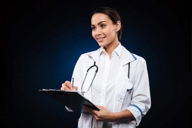 Positieve jonge in klembord schrijven en arts die opzij kijken