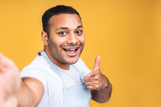 Positieve jonge indische afro-amerikaanse man die lacht en selfie maakt op smartphonecamera, blogger communiceert, video opneemt voor volgers in sociale netwerken. geïsoleerd op gele achtergrond.