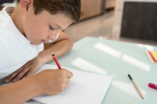 Positieve jonge jongen die zijn huiswerk doet