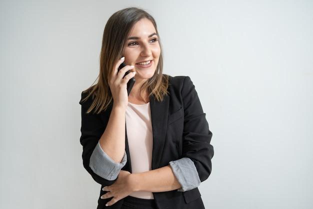 Positieve jonge kaukasische onderneemster die op telefoon spreekt