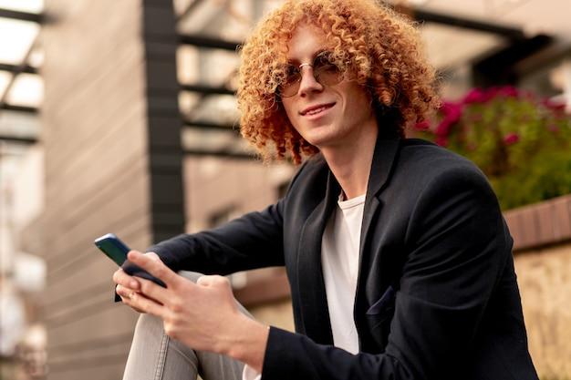 Positieve jonge kerel met gember krullend haar glimlachend en wegkijken terwijl rustend op straat in de stad en het browsen op mobiele telefoon