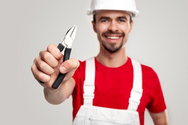 Positieve jonge klusjesman in overall en bouwvakker die een tang demonstreert en vriendelijk lacht terwijl hij bouwgereedschap en service vertegenwoordigt