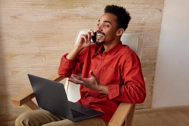 Positieve jonge knappe bebaarde brunette man met donkere huid zittend in een stoel voor raam en met een aangenaam telefoongesprek, geïsoleerd op interieur