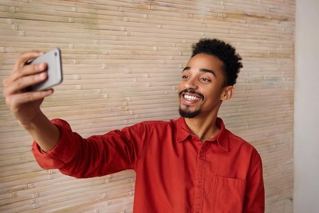 Positieve jonge kortharige bebaarde brunette man met donkere huid hand opsteken met smartphone terwijl gelukkig lachend, geïsoleerd op beige interieur