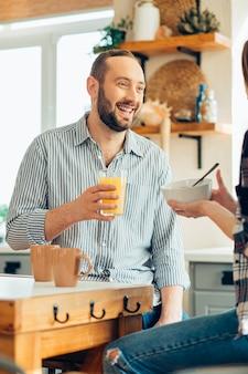 Positieve jonge man die een glas sap vasthoudt en lacht naar een vriendin