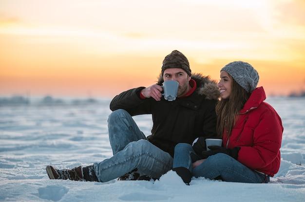 Positieve jonge man en vrouw in warme uitloper met thermos zittend op sneeuw en warme drank drinken op platteland