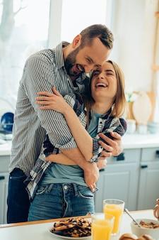 Positieve jonge man en vrouw knuffelen in de keuken en zien er gelukkig uit