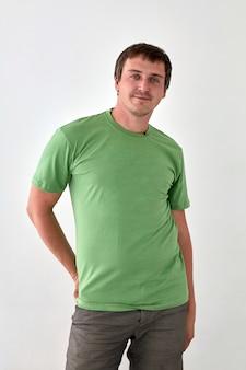 Positieve jonge man in casual outfit staande op witte achtergrond