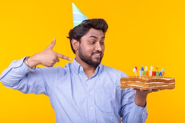 Positieve jonge man met een gelukkige verjaardagstaart poseren op een gele muur.