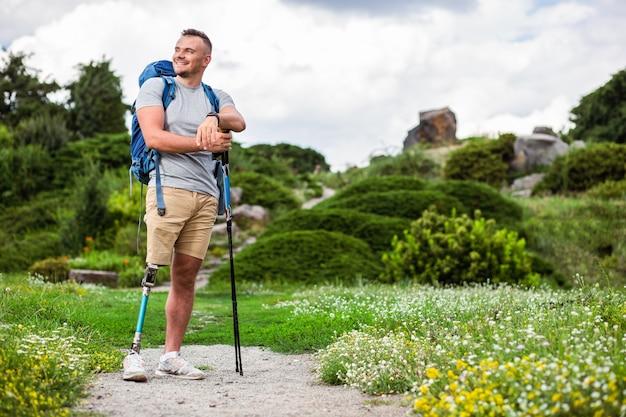 Positieve jonge man met prothese die buiten staat terwijl hij geniet van het toerisme