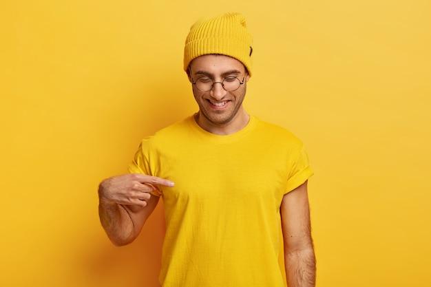 Positieve jonge man wijst naar lege ruimte van t-shirt, toont ruimte voor uw ontwerp of logo, glimlacht graag, draagt een bril, gele outfit, naar beneden gericht